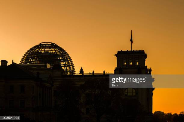 berlin sunset: silhouetted reichstag (german parliament building) - berlin, germany - demokratie stock-fotos und bilder