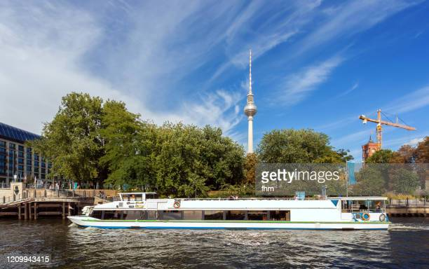 berlin television tower with a sightseeing boat on spree river in the foreground (berlin, germany) - tourboat stock pictures, royalty-free photos & images