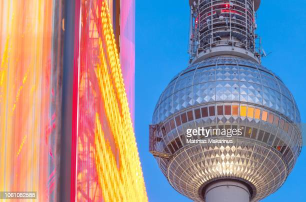 berlin television tower with colorful futuristic ferris wheel in motion - makarinus stock photos and pictures