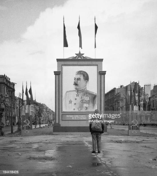 The Capture And Aftermath Of War 19451947 A German civilian looks at a vast painting of Stalin on the UnterdenLinden in Berlin 3 June 1945