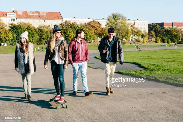 berlin: young adults with skateboards on tempelhofer feld - tempelhof airport stock pictures, royalty-free photos & images