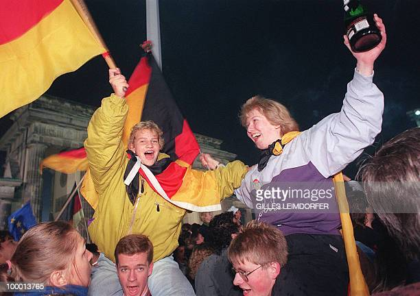Berliner youths wave German flags during the celebration of the country's reunification at the Brandenburg Gate in Berlin 03 October 1990 Fortyfive...
