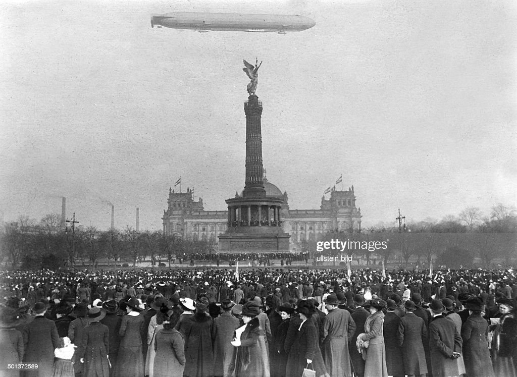 Berlin, zeppelin 'Hansa' over the Berlin Victory Column (Siegessaeule). Crowd waiting for the Danish royal couple. - 24.02.1913 : News Photo