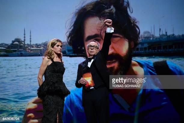 Berlinale Director Dieter Kosslick and host Anke Engelke speak in front of a picture of Deniz Yucel Turkey correspondent of German newspaper 'Die...