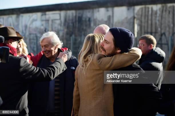 Berlinale director Dieter Kosslick greets festival director Paul Verhoeven with actress Sienna Miller and Daniel Bruehl in front of the Berlin wall...