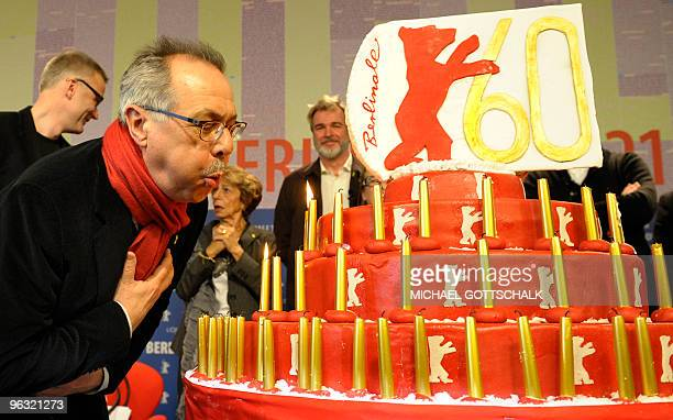 Berlinale festival director Dieter Kosslick blows the candles on a birthday cake on February 1, 2010 in Berlin, ahead of the presentation of the 60th...