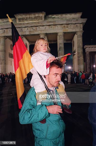 A Berliner carries his daughter on his shoulders both holding German flags standing in front of the Brandenburg Gate in Berlin 03 October 1990 as...