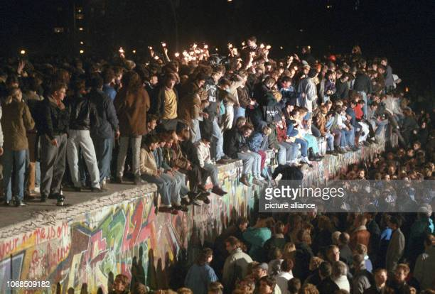 Berliners and people from all over Germany celebrate with sparklers on the Berlin Wall on November 11th 1989. After the GDR leadership had opened...