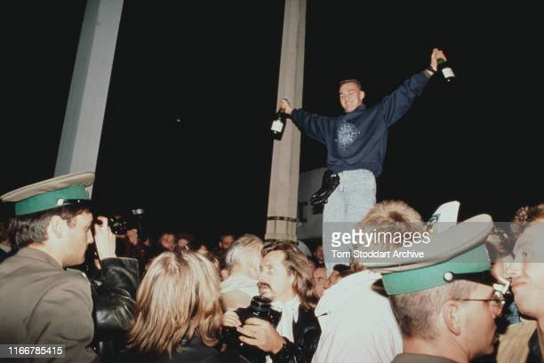 Berliners celebrate at midnight at Checkpoint Charlie on the night of 9th November 1989 when East Berliners were allowed to cross into the west for...
