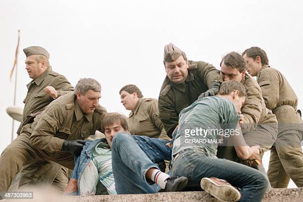 Berliners confront with East German policemen atop the Berlin Wall early 11 November 1989 near the Potsdamer Square Two days before Gunter Schabowski...