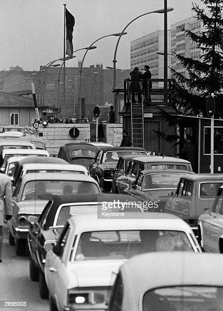 Berliners wait patiently by their cars to pass through the checkpoint on their way from West Berlin to East Berlin
