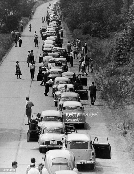 Berliners wait patiently by their cars to pass through the checkpoint on their way from West Berlin to the Federal Republic