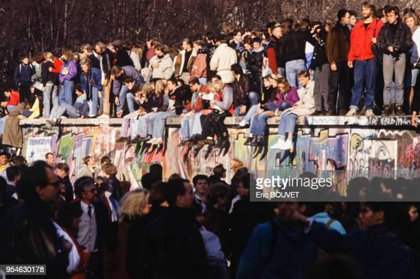 Berlinois assis sur le mur lors de la chute du Mur de Berlin le 10 novembre 1989, Allemagne.