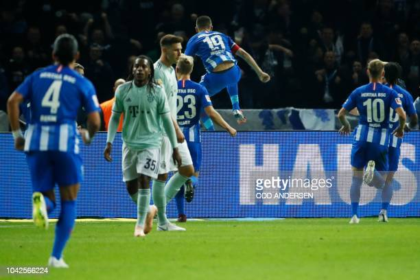 Berlin's Bosnian forward Vedad Ibisevic jumps over the advertisement hoarding while celebrating scoring a penalty during the German first division...