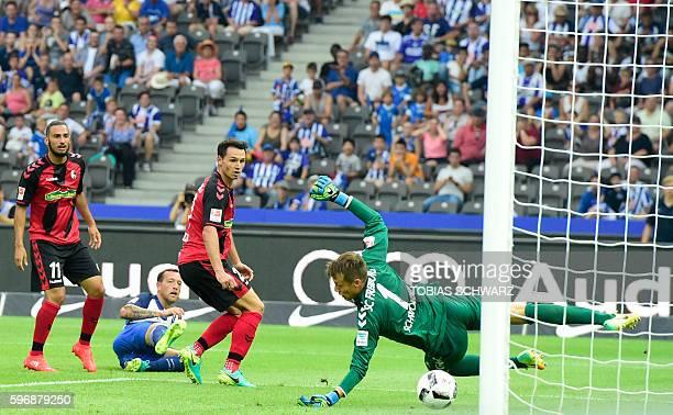 Berlin's forward Julian Schieber scores against Freiburg's midfielder Nicolas Hoefler , Freiburg's midfielder Onur Bulut and Freiburg's goalkeeper...