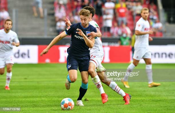 Berlin's German defender Lukas Kluenter and Cologne's German defender Jonas Hector vie for the ball during the German first division Bundesliga...