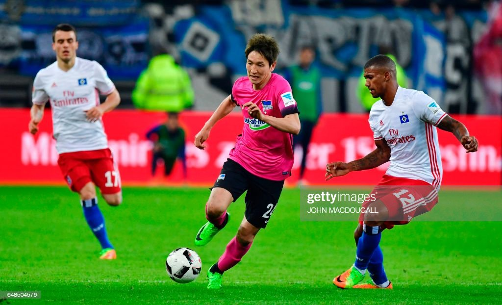 Berlin's Japanese midfielder Genki Haraguchi (C) vies with Hamburg's Brazilian midfielder Walace (R) during the German First division Bundesliga football match between Hamburger SV and Hertha BSC Berlin, on March 5, 2017. / AFP PHOTO / John
