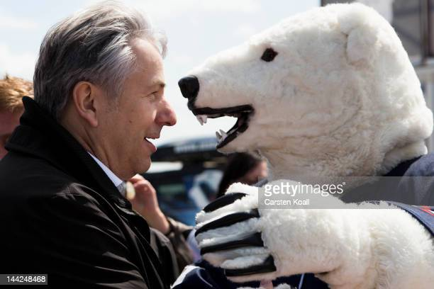 Berlin's major Klaus Wowereit stands face to face wih the mascot of the Berlin ice hockey club at the open house weekend next to the construction...
