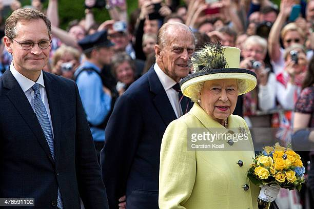Berlin's Major Michael Mueller leads Queen Elizabeth II and Prince Philip Duke of Edinburgh past the Brandenburg Gate on the final day of a four day...