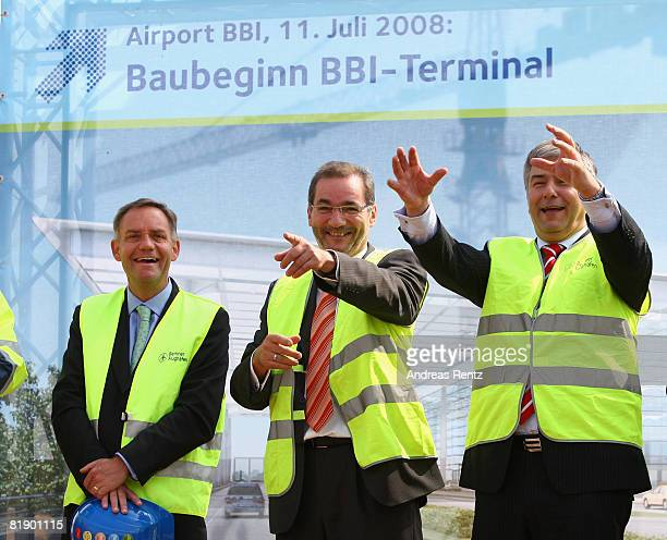 Berlin's mayor Klaus Wowereit and Brandenburg's State Governor Matthias Platzeck gesture as Rainer Schwarz of BBI smiles during an official ceremony...