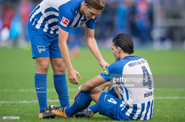Berlin's Niklas Stark tries to help up teammate Karim Rekik after the German Bundesliga football match between Hertha BSC and FC Schalke 04 in Berlin...