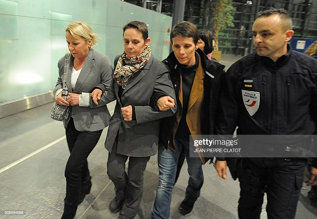 Bernadette Dimet (C) flanked by relatives walks free out of the courtroom on February 5, 2015 in Grenoble, eastern France. The court of Grenoble handed a suspended five-year jail sentence to Dimet who shot dead her abusive husband, less than a week after President Francois Hollande pardoned a woman jailed in a similar case. / AFP / JEAN