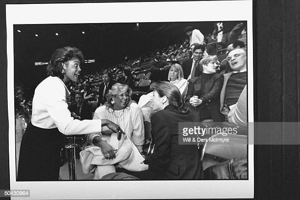 Bernadette LockeMattox asst basketball coach at Univ of KY chatting w Joanne Pitino wife of head coach Rick Pitino an unident woman who are sitting...