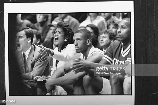 Bernadette LockeMattox asst basketball coach at Univ of KY screaming at her team as she sits on bench w fellow asst coach Billy Donovan several...