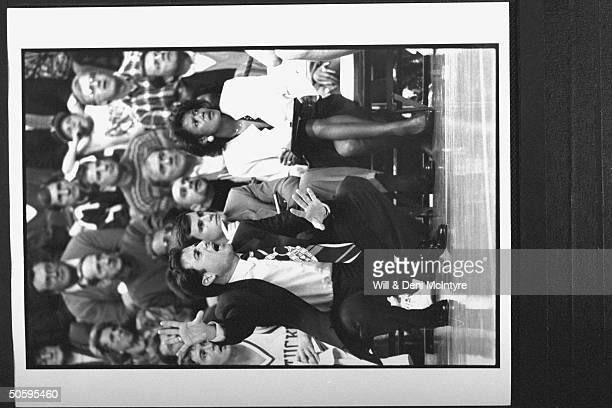 Bernadette LockeMattox asst basketball coach at Univ of KY tensely holding clipboard while sitting on bench w asst coach Billy Donovan as head coach...