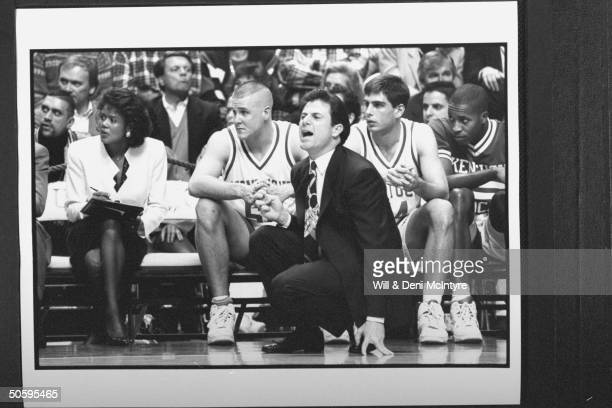 Bernadette LockeMattox asst basketball coach at Univ of KY tensely holding clipboard while sitting on bench w players as head coach Rick Pitino...