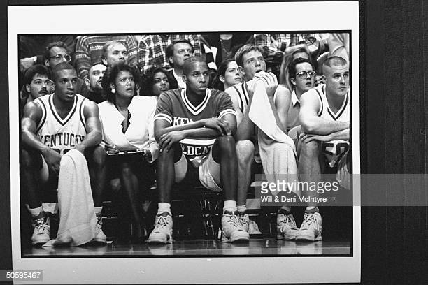 Bernadette LockeMattox asst basketball coach at Univ of KY tensely holding clipboard while sitting on bench w players during game against TN at Rupp...