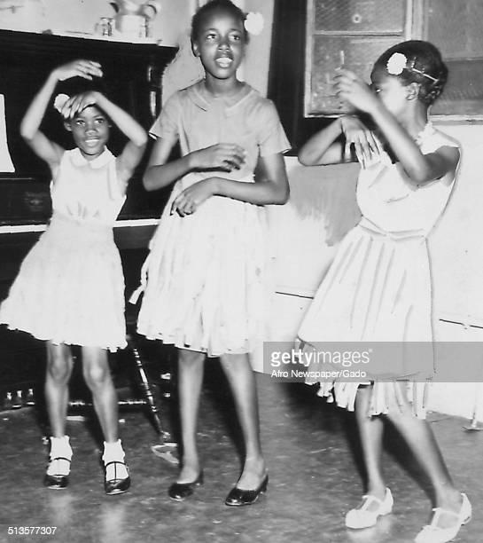 Bernadette Matthews Jennifer Jones Gladys Ridall and African American schoolchildren during a talent show August 23 1959