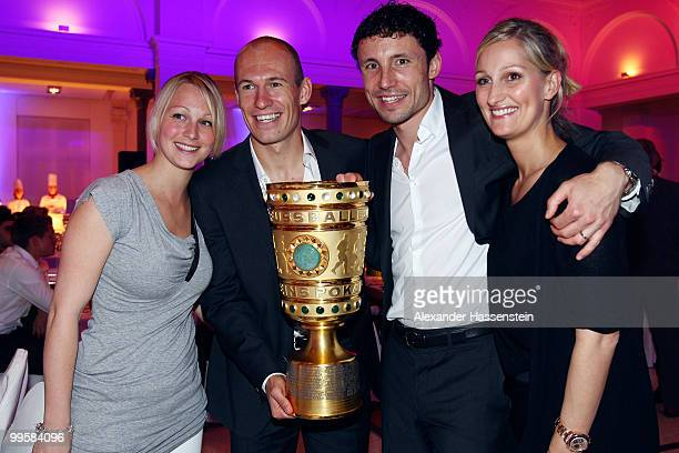 Bernadien and Arjen Robben as well as Mark van Bommel and his wife Andra pose with the trophy the Bayern Muenchen Champions Party after the DFB Cup...