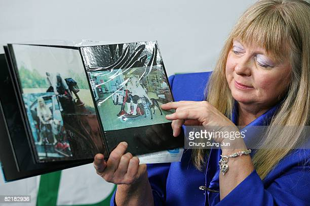 Bernann Mckinney shows the photos of her former pit bull terrier at the Seoul National University on August 5 2008 in Seoul South Korea The Seoul...