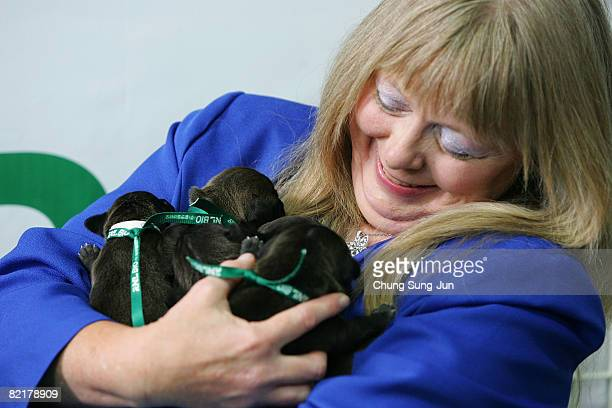 Bernann Mckinneya pet owner holds her pit bull terrier cloned dogs at the Seoul National University on August 5 2008 in Seoul South Korea The Seoul...