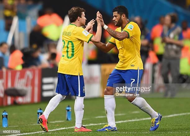Bernard and Hulk of Brazil high five as Bernard enters the match during the 2014 FIFA World Cup Brazil Group A match between Brazil and Croatia at...