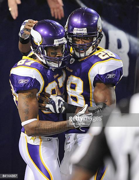 Bernard Berrian of the Minnesota Vikings is congratulated by teammate Adrian Peterson following a touchdown during an NFL game against the New York...