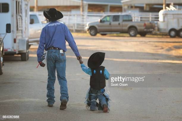 Bernard Daniels walks with his grandson Zion Williams before the start of competition at the Bill Pickett Invitational Rodeo on April 1 2017 in...