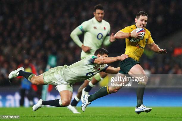 Bernard Foley of Australia breaks through the England defence being tackled by Ben Youngs of England during the Old Mutual Wealth Series match...