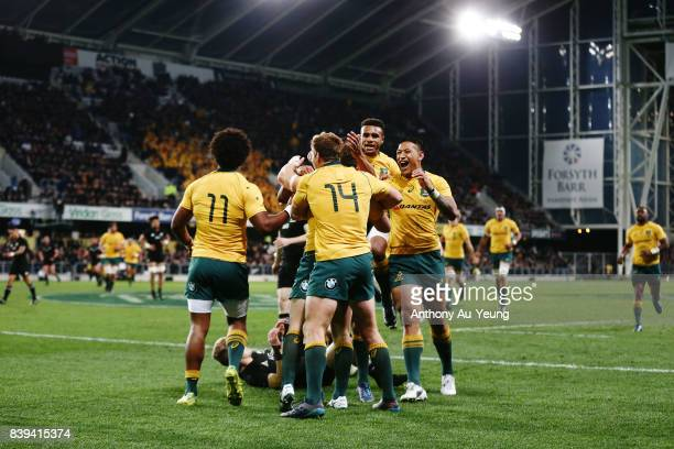 Bernard Foley of the Wallabies celebrates with teammates after scoring a try during The Rugby Championship Bledisloe Cup match between the New...