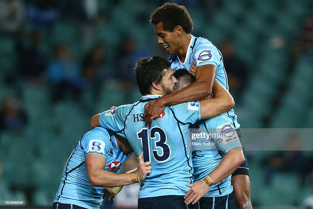 Bernard Foley of the Waratahs is congratulated by Adam Ashley-Cooper and Ben Volavola of the Waratahs after scoring a try during the round three Super Rugby match between the Waratahs and the Rebels at Allianz Stadium on March 1, 2013 in Sydney, Australia.