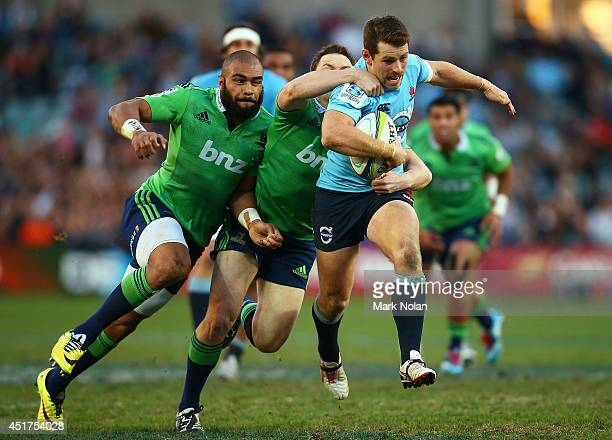 Bernard Foley of the Waratahs is tackled after making a line break during the round 18 Super Rugby match between the Waratahs and the Highlanders at...