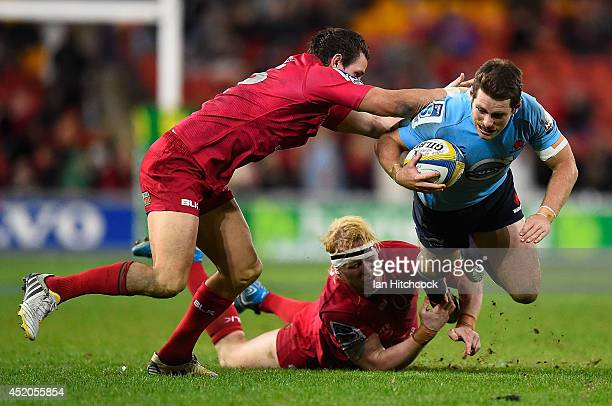 Bernard Foley of the Waratahs is tackled by Beau Robinson and Mike Harris of the Reds during the round 19 Super Rugby match between the Reds and the...
