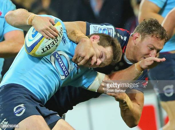 Bernard Foley of the Waratahs is tackled high by Scott Higginbotham of the Rebels during the round 15 Super Rugby match between the Rebels and the...