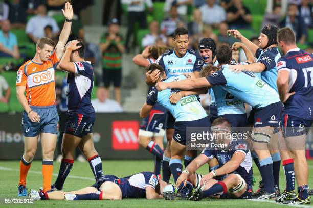 Bernard Foley of the Waratahs scores the winning try as teammates come in to celebrate during the round five Super Rugby match between the Rebels and...
