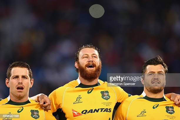 Bernard Foley Scott Higginbotham and Adam AshleyCooper of the Wallabies sing the Australian national anthem during The Rugby Championship match...