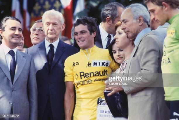 Bernard Hinault revêtu du maillot jaune entouré des hommes politiques JeanPierre Soisson et Maurice Couve de Murville lors de sa victoire dans le...