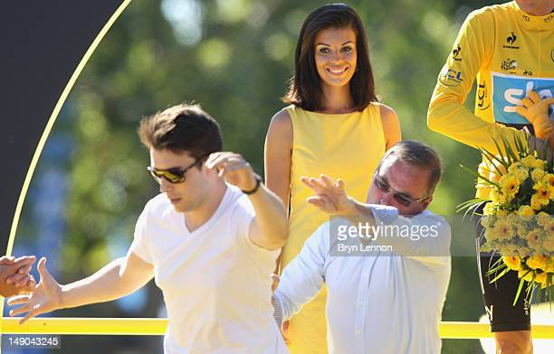Bernard Hinault throws a podium invader off the stage after the twentieth and final stage of the 2012 Tour de France, from Rambouillet to the...