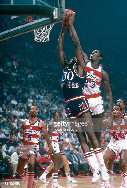 Bernard King of the New York Knicks goes up to shoot in front of Charles Davis of the Washington Bullets during an NBA basketball game circa 1983 at...