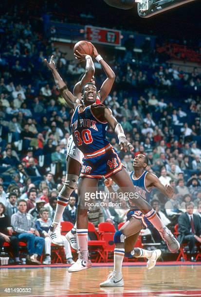 Bernard King of the New York Knicks jumps at shooter Cliff Robinson of the Washington Bullets during an NBA basketball game circa 1985 at the Capital...